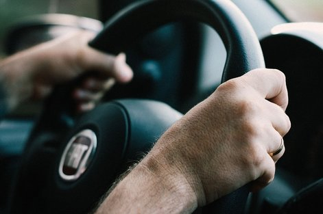 Man holding a car's steering wheel
